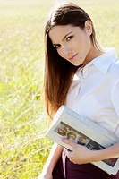 Portrait of a teenage girl holding a newspaper in a field