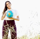 Businesswoman holding a globe in a field