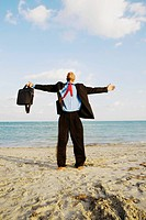 Businessman standing on the beach with his arms outstretched