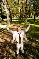 Businessman with his arms raised in a park