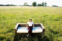 Businesswoman sitting on a sofa in a grassland