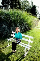 Businesswoman working on a laptop in a lawn