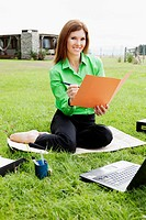 Businesswoman working in a lawn