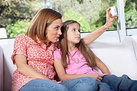 Woman with her daughter taking a photograph of themselves with a digital camera