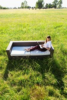 Businesswoman using a laptop on a sofa in a grassland