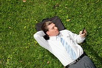 Businessman lying in a park and using a mobile phone