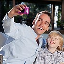 Man with his son taking a picture of themselves with a digital camera