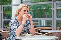 Pretty blond girl eating a bagel