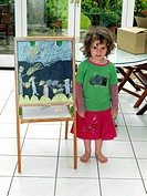 Young Girl Drawing With Chalk On Blackboard