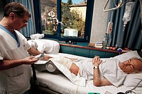 Physiotherapy after knee surgery. Physiotherapist operating a Mobilimb device. This device is used to keep a joint that is unable to bear weight mobil...