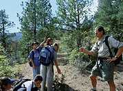 Natural history education. Park ranger explaining biology to teenagers using a pine cone. Photographed in Beaulah State Park, Colorado, USA.