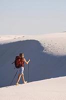 A woman hiking across sand dunes.