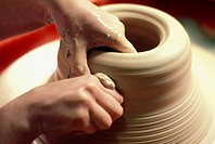 close up of a potter's hands as he carefully shapes his clay on the turning wheel