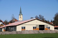 Farm in front of a village church in Bavaria