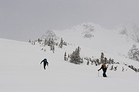 Two adults ski_tour in mountains.