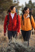 Two women hike on trail through sage brush.