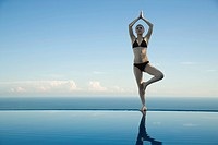 Woman standing in tree pose on edge of infinity pool