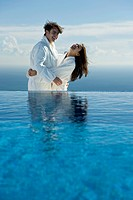 Couple embracing and laughing at edge of infinity pool, both wearing bathrobes