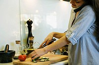 Woman talking on phone while chopping vegetables