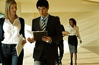 Business associates walking and discussing documents