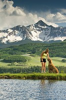 A woman petting her dog below Mount Wilson, Telluride, Colorado.