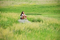 Young woman sitting on rock in a bright green field at Spirit Mound, South Dakota.