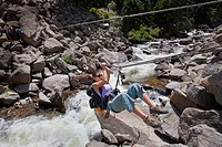 A woman pulls herself across Boulder Creek on a tyrolean traverse line.