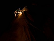 Descending at night, a young man cleans up the trad gear while rock climbing in Moab, Utah.