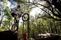 A Trials rider prepares to leap off a rock at Toohey Forest, Brisbane, Queensland, Australia.