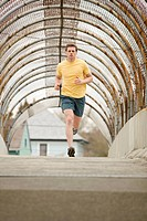 An athletic male jogging through a pedestrain overpass.