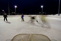 A family plays a game of pick_up hockey at the local elementary school´s ice skating rink in Anchorage, Alaska.