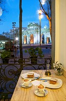 Coffee with cake for two at dusk. Independencia Square, Madrid, Spain.