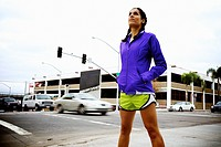 A female runner stands on the corner of two streets and cars pass by in the background creating motion blur in San Diego.