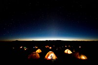 Tents illuminate the night as stars fill the sky on mMt. Kilimanjaro.