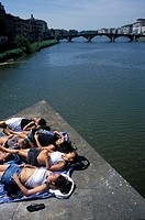 A group of girls sunbathing on one of the bridges over the river