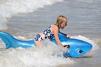 Six year old girl at the beach playing in the surf on inflatable shark Mimiwhangata Northland, New Zealand