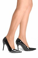 A woman's legs and feet in black patent leather stilletto high heel shoes