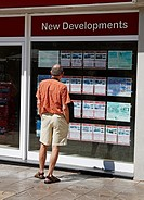 Tourist looking at Estate agents window in Puerto de Mogan, Canary Islands, Spain