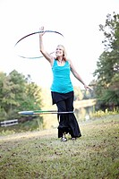 A mature woman twirls a hula hoop over her head and around her leg while exercising in Chelsea, Alabama.