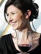 Germany, Munich, Mature woman with wine glass, smiling