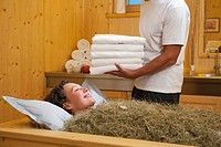 Italy, South Tyrol, Woman having hay bath in hotel urthaler