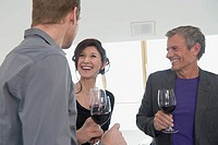 Germany, Munich, Men and woman drinking wine, smiling