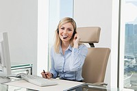 Germany, Frankfurt, Business woman wearing headset, smiling, portrait