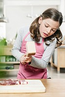 Germany, Cologne, Girl cutting meat using meat tenderiser