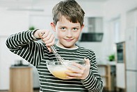 Germany, Cologne, Boy beating batter in bowl, portrait