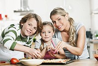 Germany, Cologne, Mother and children making pizza in kitchen