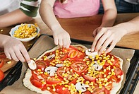 Germany, Cologne, Mother and children garnishing pizza