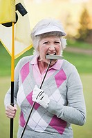 Italy, Kastelruth, Mature woman with golf club and golf flag on golf course