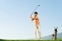 Italy, Kastelruth, Mid adult woman playing golf on golf course