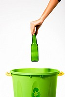 Woman´s hand putting a glass bottle into a recycling bin